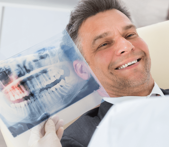 man smiling with dental x rays